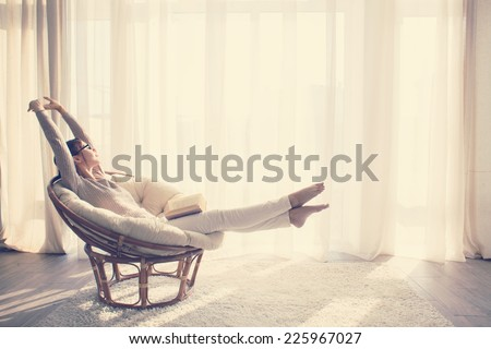 Young woman at home sitting on modern chair in front of window relaxing in her living room reading book, instagram toning - stock photo
