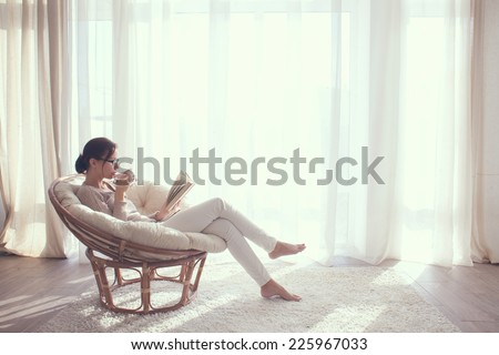 Young woman at home sitting on modern chair in front of window relaxing in her living room reading book and drinking coffee or tea - stock photo