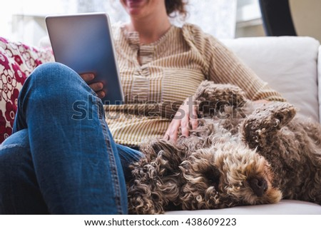 Young woman at home with a tablet and a dog - stock photo