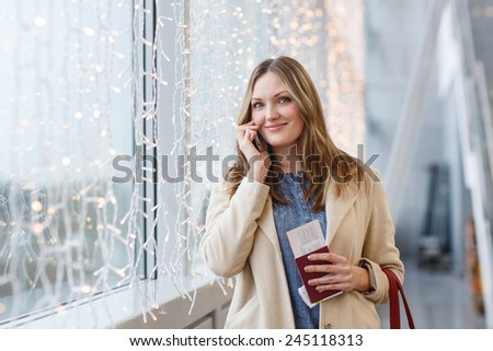 Young woman at international airport, having telephone conversation call via mobile phone and holding her passport while waiting for her flight. Female passenger at terminal, indoors. - stock photo