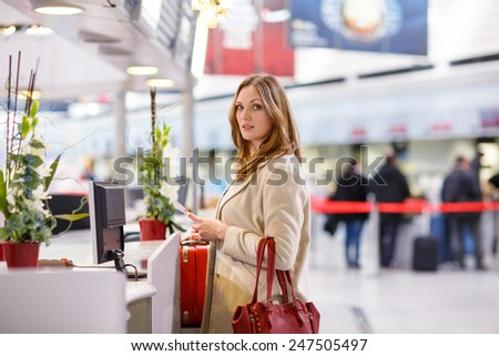 Young woman  at international airport, on check in counter and waiting for her flight. Female passenger with red suitcase and passport at departure terminal, indoors. - stock photo