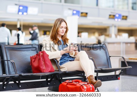 Young woman at international airport sitting waiting for cancelled or delayed flight. Female passenger at terminal, indoors.  Travel, business, people concept. - stock photo