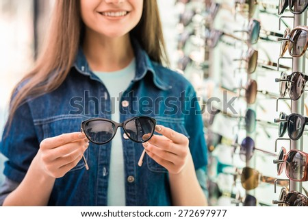 Young woman at optician with glasses is looking for sunglasses. - stock photo