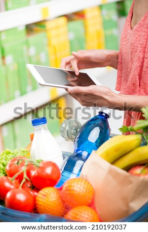 Young woman at supermarket shopping with digital tablet and full basket on foreground. - stock photo