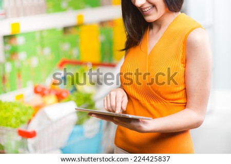 Young woman at supermarket shopping with digital tablet and shelves on background. - stock photo