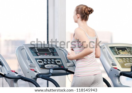 Young woman at the gym exercising. Run on a machine - stock photo