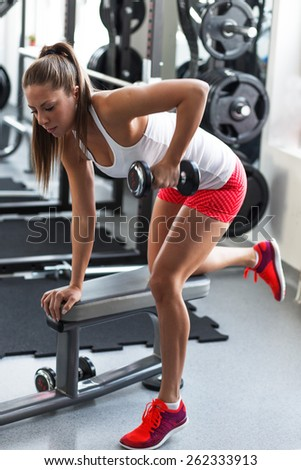 Young woman at the gym  working on her triceps and back - stock photo