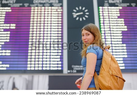 Young woman at the international airport, with flight board on background - stock photo