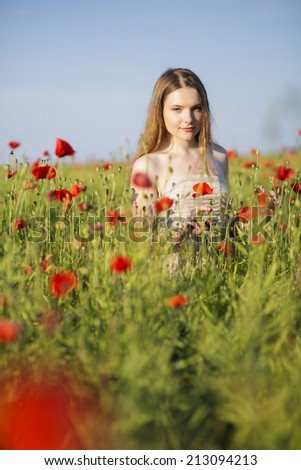 Young woman at white dress at poppies field - stock photo