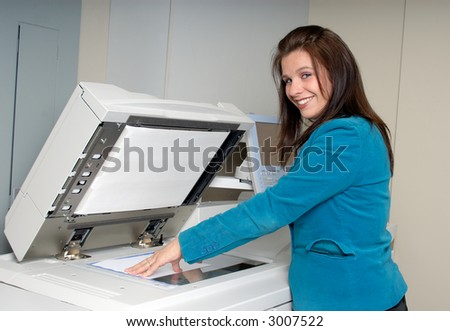 Young Woman At Work In The Photocopier Room At Her Office - stock photo