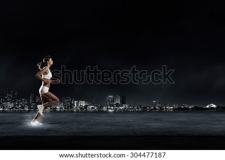 Young woman athlete running fast on dark background  - stock photo