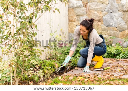Young woman autumn gardening backyard planting tools housework flowerbed - stock photo
