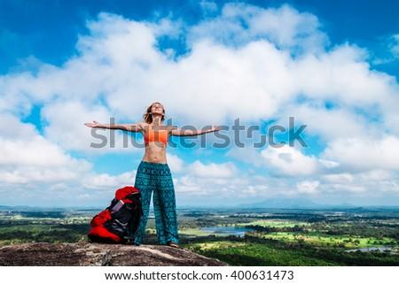 Young woman backpacker on the top of mountain Pidurangala, Sri-Lanka - stock photo