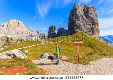 Young woman backpacker tourist on mountain trail near Cinque Torri rock formation, Cortina d'Ampezzo, Dolomites Mountains, Italy - stock photo
