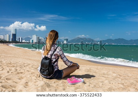 Young woman barefoot on the beach relaxing in yoga pose - stock photo
