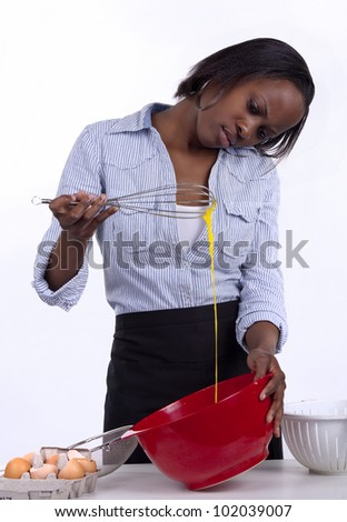 Young woman beating an egg with a whisk and checking consistency. - stock photo