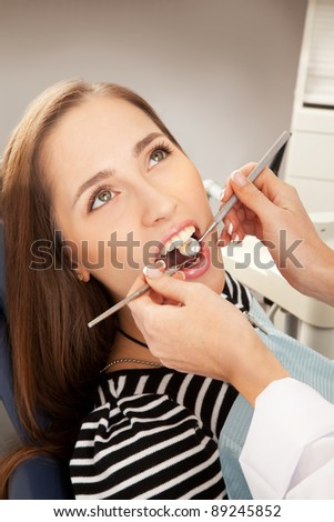 Young woman being examined by a dentist - stock photo