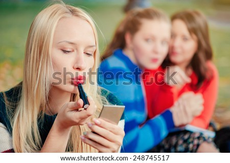 Young woman being gossiped about. Young beautiful blond woman doing make up while her friends communicating on background. - stock photo