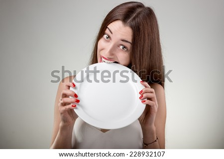 Young woman bites empty plate. Hungry woman with plate in studio on white background - stock photo