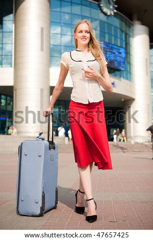 Young woman, blond, against the backdrop of the station. In all growth. - stock photo