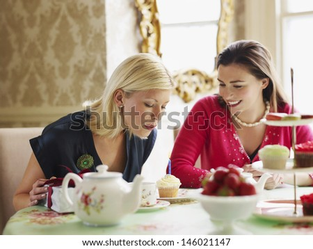 Young woman blowing candle on cupcake by friend at dining table - stock photo