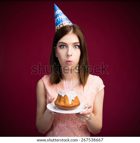 Young woman blowing candles on her cake over pink background. Looking at camera - stock photo