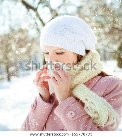 Young woman blowing her nose into a tissue in winter  - stock photo