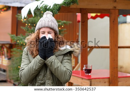 Young woman blowing her nose on a handkerchief while standing on an christmas market, conceptual of a illness, flu, cold, allergic rhinitis or hay fever - stock photo