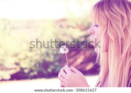 young woman blowing on a dandelion and making a wish outdoors in a garden, custom color tone,s pinkish retro filters applied. - stock photo