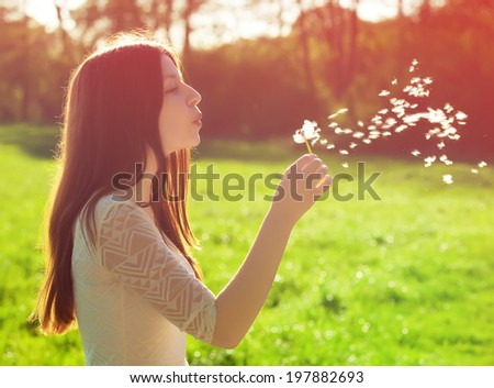 young woman blowing on a white dandelion - stock photo