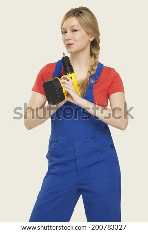 Young woman blowing power drill smiling - stock photo