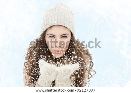 Young woman blowing snowflakes from hands - stock photo