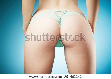 Young woman body in pretty panties on blue background - stock photo