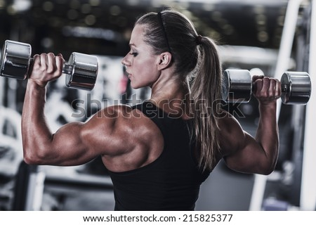 Young woman bodybuilder with dumbbells. - stock photo