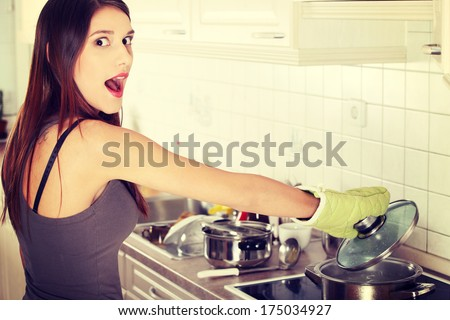 Young woman boiling something in pot (preparing dinner)  - stock photo