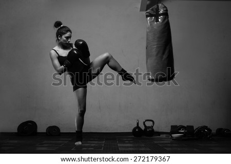 Young woman boxing workout in an old dark gym - stock photo