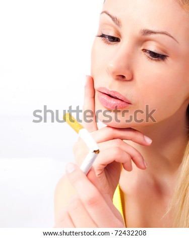 young woman breaking a cigarette and frowning, isolated against white background - stock photo