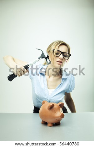 Young woman breaking a piggy bank - stock photo