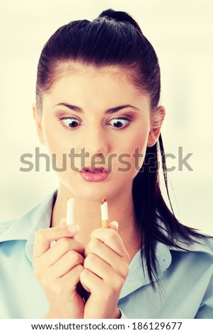 Young woman breaking cigarette - stock photo