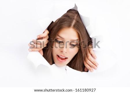 Young woman breaking through a paper sheet. - stock photo