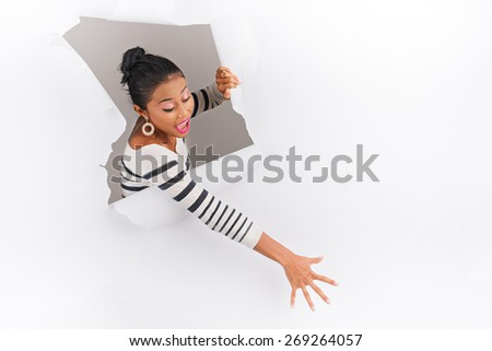 Young woman breaking through paper and reaching for something - stock photo
