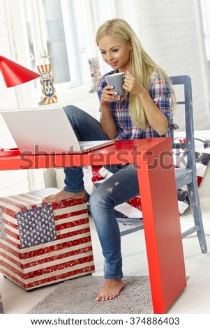 Young woman browsing internet on laptop at home, drinking tea. - stock photo