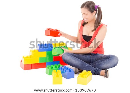 young woman building with colorful blocks - stock photo