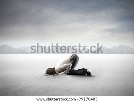 Young woman burying her head in the sand - stock photo