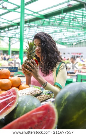 Young woman buying fruit at the market - stock photo