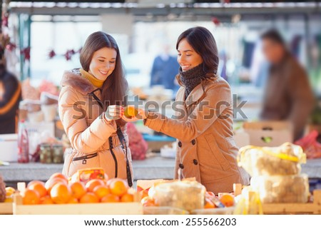 Young woman buying organic mandarin on the market - stock photo