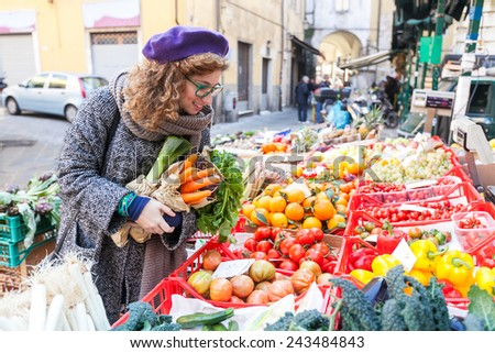 Young Woman Buying Vegetables at Local Market - stock photo
