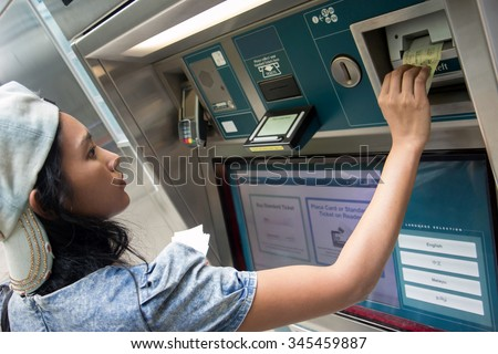Young woman buys a ticket vending machine. Purchase tickets in public transport ticket vending machine. Payment ticket subway vending machine. Asian tourist buys a ticket for train at vending machine. - stock photo