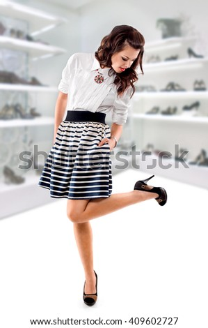 young woman buys shoes in a shoe store, shopping concept - stock photo