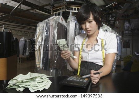 Young woman calculating bills with calculator in laundry - stock photo